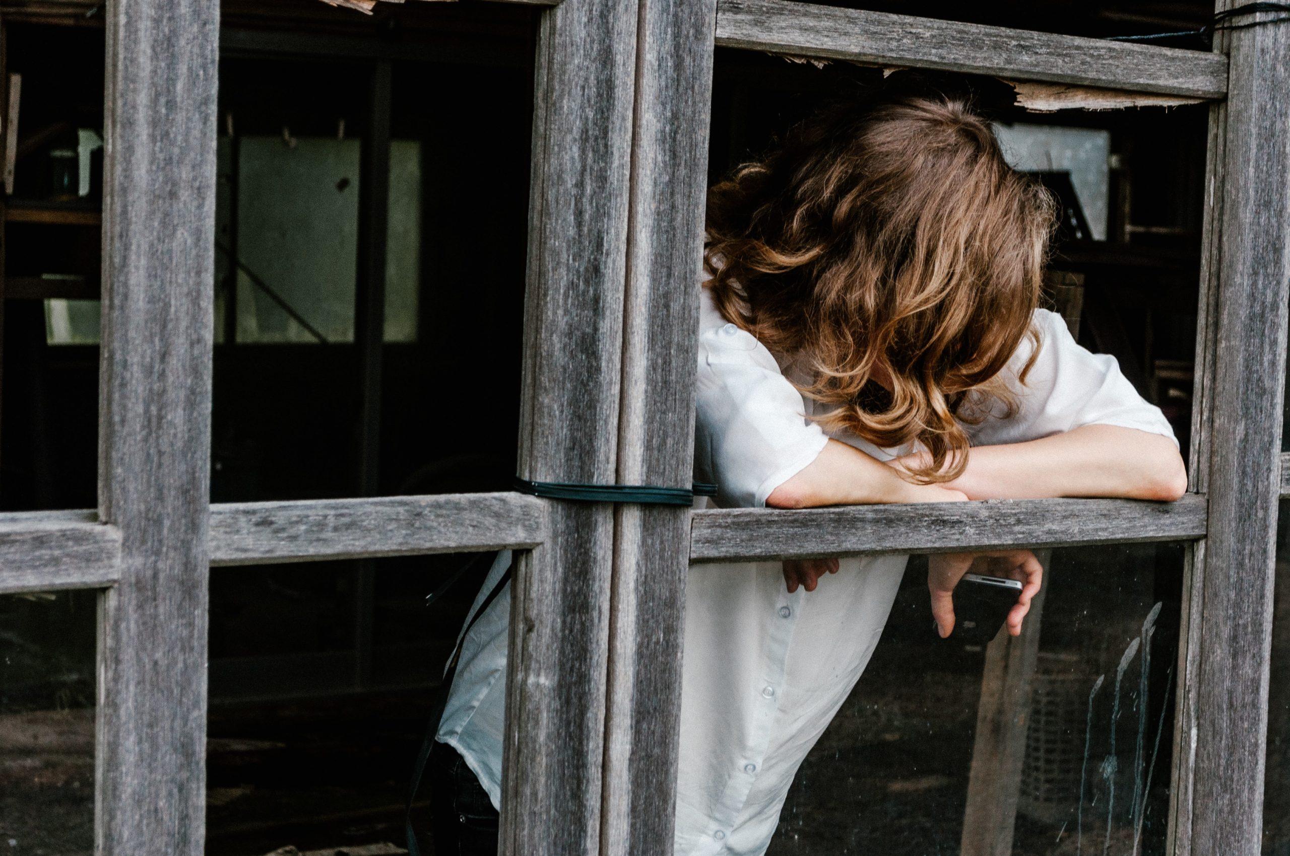 Kvinne ser ut av vinduet, håpløshet, angst.